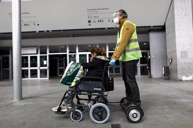 Un trabajador sanitario protegido lleva en silla de ruedas al exterior del hospital de campaña montado en Ifema