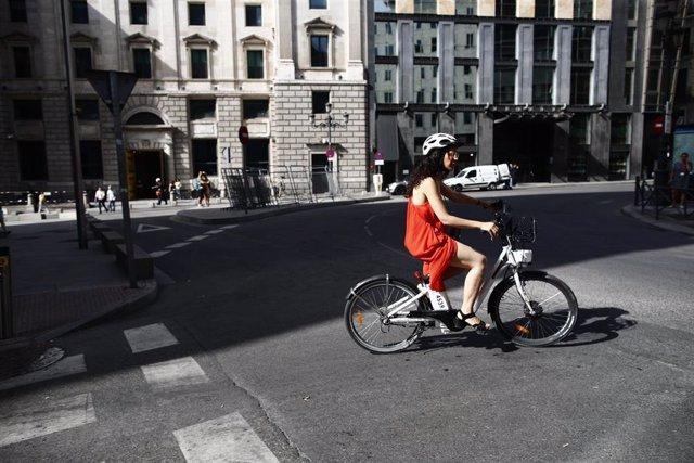 Una ciclista pasea con una bicicleta eléctrica cerca del Congreso de los Diputados. Archivo.