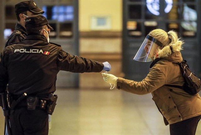 Un policía nacional entrega una mascarilla a una mujer en el vestíbulo de la estación del Norte de Valencia el día en el que se reactiva la actividad laboral no esencial en las empresas cuyos empleados no puedan teletrabajar. 14 de abril de 2020.