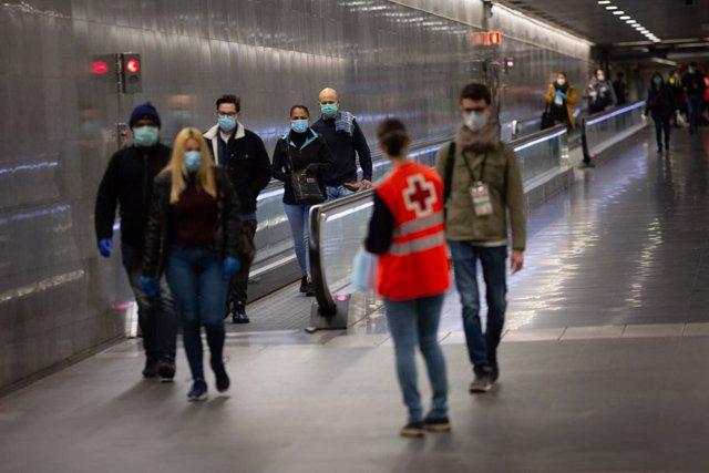 Una voluntària de Creu Vermella entrega mascarillas als passatgers en l'estació catalana de Diagonal el dia en el qual es reactiva l'activitat laboral no essencial a Catalunya en les empreses que els seus emprats no puguin teletrabajar quan es compleix un