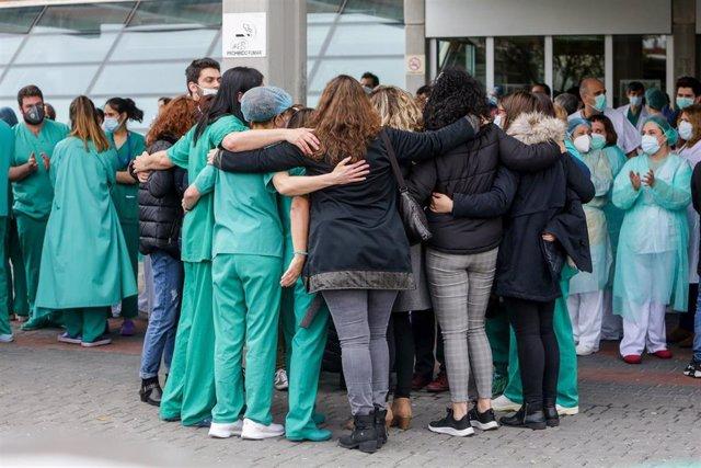 Sanitarios del Hospital Severo Ochoa de Leganés se abrazan durante el homenaje al enfermero de quirófano de 57 años fallecido por Covid-19. En Leganés/Madrid (España) a 13 de abril de 2020.