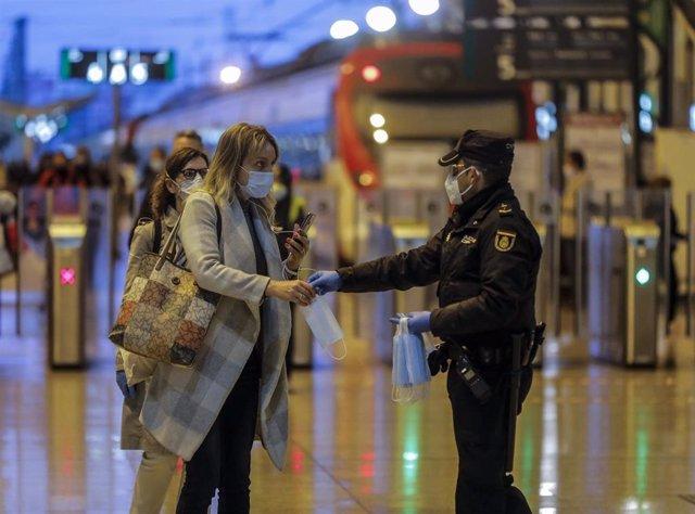 Un policía nacional entrega una mascarilla a una mujer en el vestíbulo de la estación del Norte de Valencia el día en el que se reactiva la actividad laboral no esencial en las empresas cuyos empleados no puedan teletrabajar