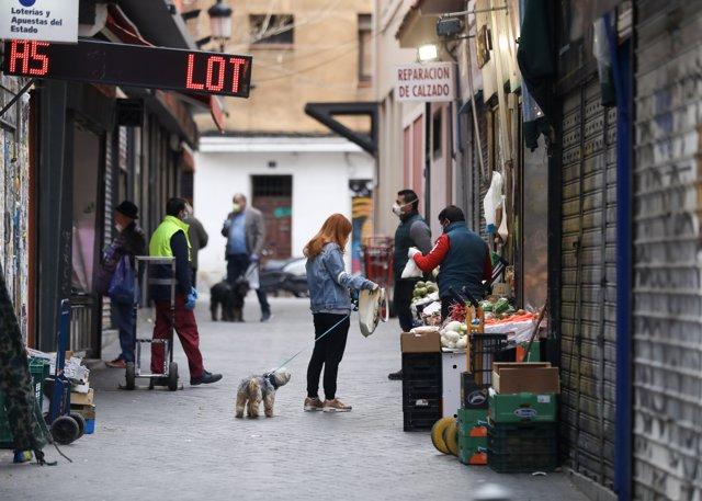 Una calle de la capital donde transeúntes realizan compras de primera necesidad en los pocos comercios abiertos, durante los inicios del segundo mes de confinamiento por la crisis del coronavirus. En Madrid, (España), a 14 de abril de 2020.