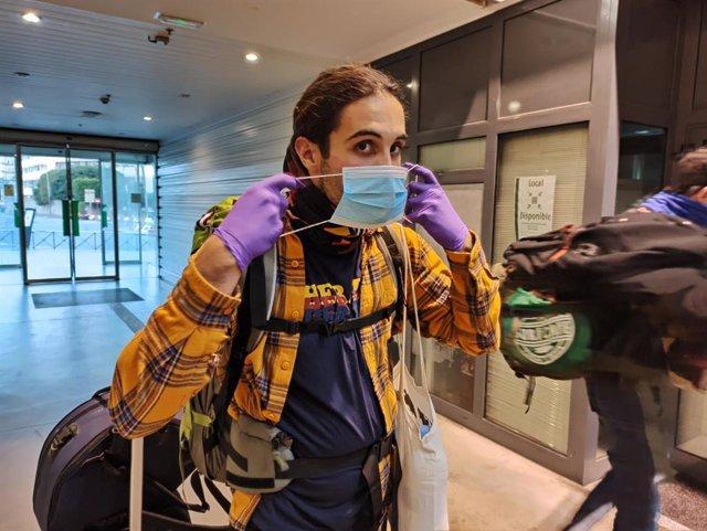 Un joven se coloca una de las mascarillas que las Fuerzas de Seguridad del Estado y voluntarios de Protección Civil han repartido en puntos clave para todos aquellos usuarios que tuvieran que utilizar el transporte público,