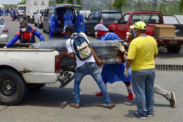 Un grupo de personas carga un ataúd en un coche en la ciudad ecuatoriana de Guayaquil durante la pandemia de coronavirus