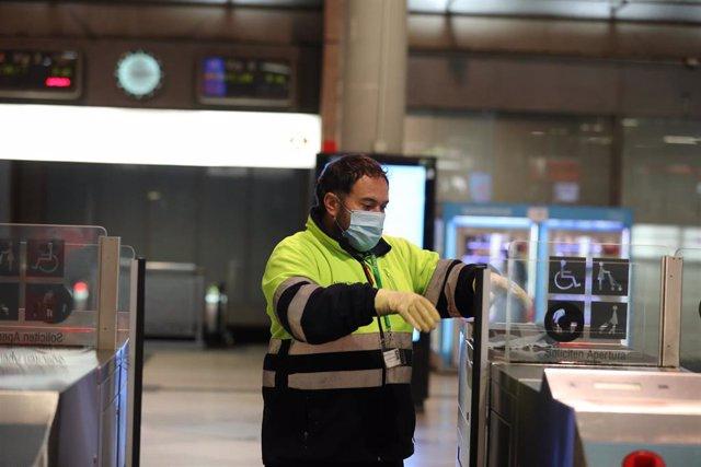 Una trabajador limpia los tornos de la estación de Cercanías de Atocha durante el segundo día de reparto de mascarillas en el transporte público por la reactivación de la actividad laboral no esencial en las empresas cuyos empleados no puedan teletrabajar