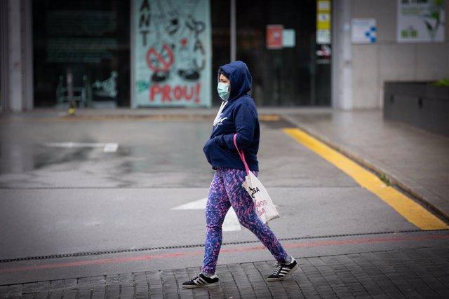 Una dona passa pels voltants de l'Estació de Barcelona Sants durant el dia en el qual entra en vigor la limitació total de moviments salvo dels treballadors d'activitats essencials, mesura adoptada ahir pel Govern com a prevenció del