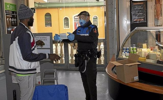 Un agente repartiendo mascarillas.