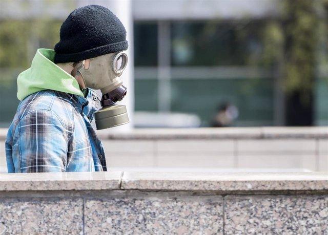 Un hombre con una máscara antigás pasea por una calle de Bratislava
