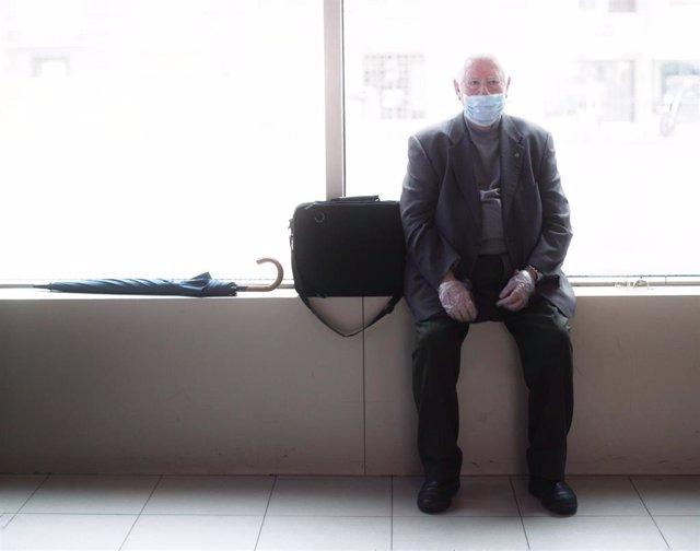 Un anciano espera cuando se cumple un mes desde el inicio del estado de alarma decretado a consecuencia del coronavirus