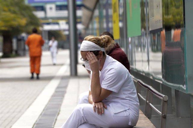 Una trabajadora sanitaria protegida se sienta en uno de los bancos de las inmediaciones del hospital de campaña montado en IFEMA.