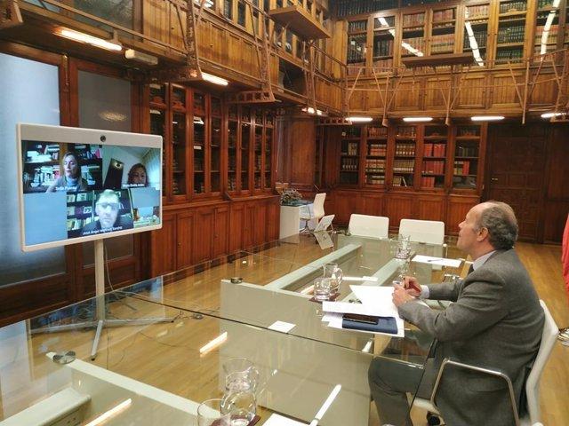 El ministro de Justicia, Juan Carlos Campo, en una reunión por videoconferencia con la decana del Colegio de Registradores, María Emilia Adán, y el presidente del Consejo General del Notariado, José Ángel Martínez Sanchiz, el 7 de abril de 2020.