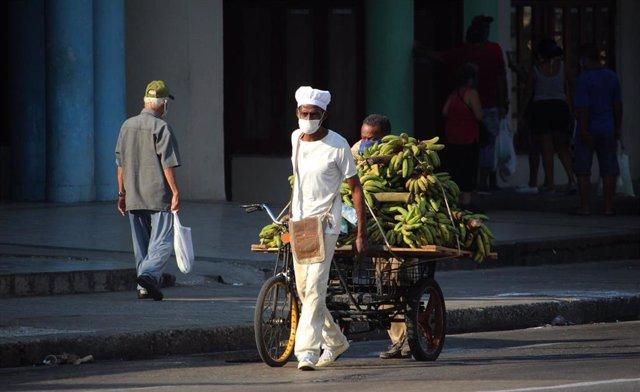 Un vendedor de bananas con mascarilla por el coronavirus en una calle de La Habana