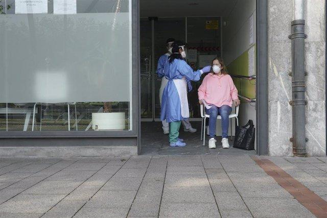 Dos sanitarios protegidos con guantes, mascarillas y pantallas protectoras recogen una muestra de una trabajadora funcionaria que ha dado positivo en Covid-19 o ha estado en riesgo de darlo, para realizar un Análisis PCR en un local de la Diputación de Bi