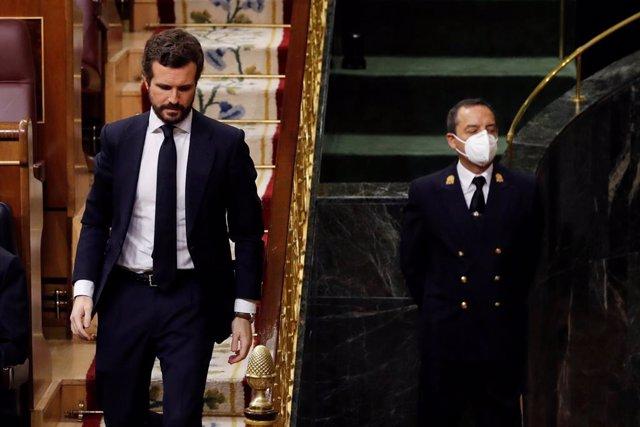 El líder del PP, Pablo Casado, pasa junto al un funcionario del Congreso protegido con una mascarilla durante la primera sesión de control al Ejecutivo celebrada en el Congreso desde que se declaró el estado de alarma el pasado 14 de marzo,