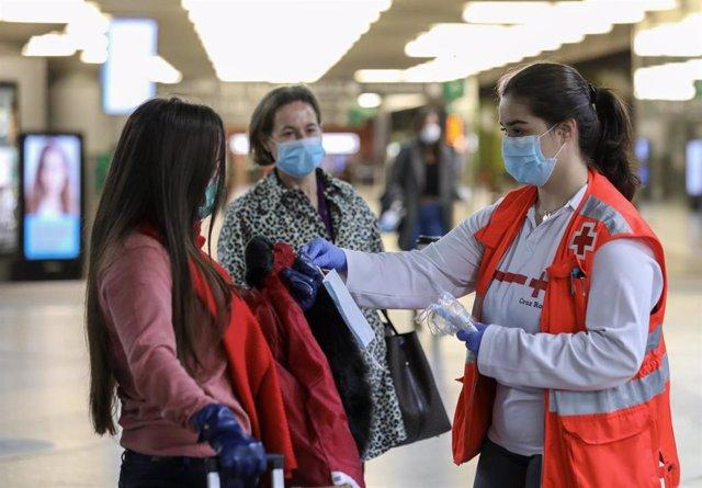 Voluntarios de Cruz Roja entregan mascarillas a pasajeros en la estación de Cercanías de Atocha, en Madrid