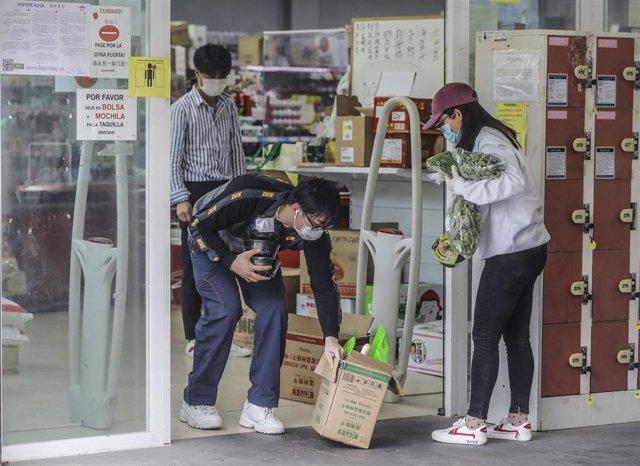 Personas de procedencia asiática salen de realizar sus compras