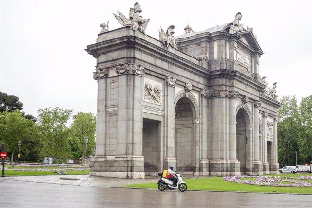 Un repartido de la empresa Glovo realiza un trayecto por la Puerta de Alcalá.