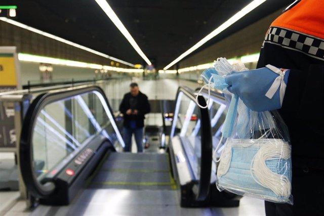 Voluntario de Protección Civil reparte mascarillas entre trabajadores usuarios del metro de Málaga. Imagen de archivo.