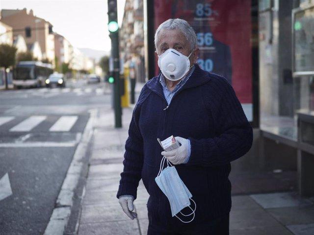 Un hombre protegido con una mascarilla espera al autobús en una marquesina durante el día 32 del estado de alarma y dos días después de que se haya reactivado la actividad laboral no esencial en las empresas cuyos empleados no puedan teletrabajar, en Pamp