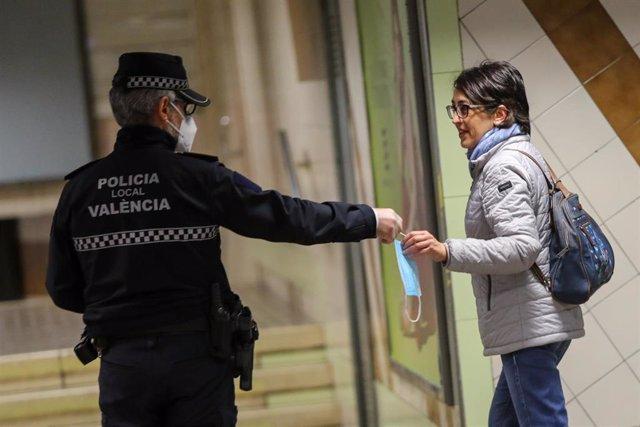 Agentes de policía local de Valencia entregan mascarillas en el metro durante el segundo día de reparto de mascarillas en el transporte público