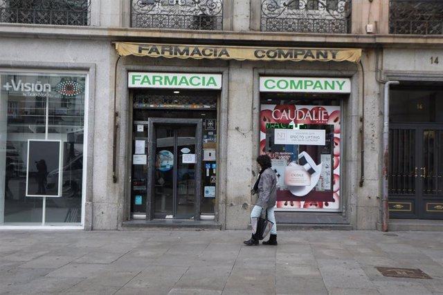 Una mujer protegida con mascarilla y guantes pasa delante de una Farmacia. En Madrid (España) a 14 de abril de 2020.
