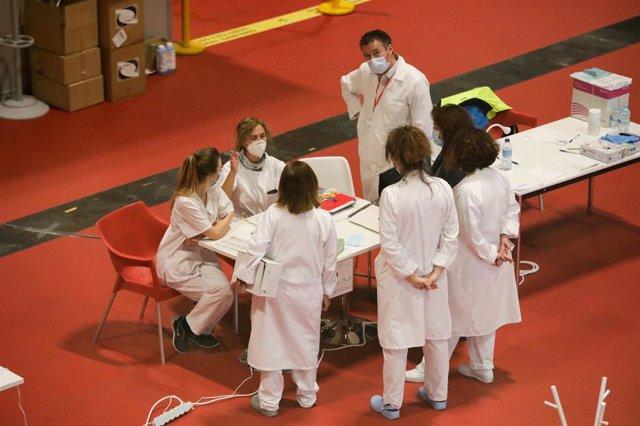 Trabajadores sanitarios protegidos hablan en el interior del hospital provisional específico sobre coronavirus montado en IFEMA.