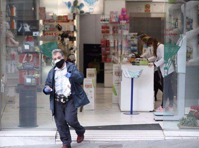 Un hombre protegido con mascarilla y guantes sale de una Farmacia. En Madrid (España) a 14 de abril de 2020.