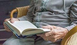 Imagen de archivo de un anciano leyendo un libro en una residencia.