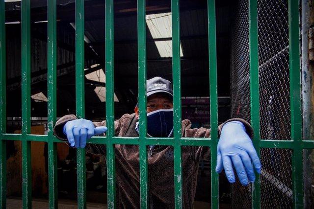 Un ciudadano ecuatoriano observa tras una verja las medidas de seguridad que ejecutan las autoridades en el distrito de San Roque, en Quito, para intentar frenar el avance del Covid-19.