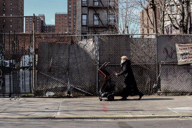 Una mujer con mascarilla andando por las calles de Nueva York