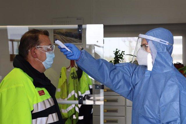 Un sanitario toma la temperatura a un trabajador antes de su jornada laboral en la planta de Opel/PSA de Figueruelas