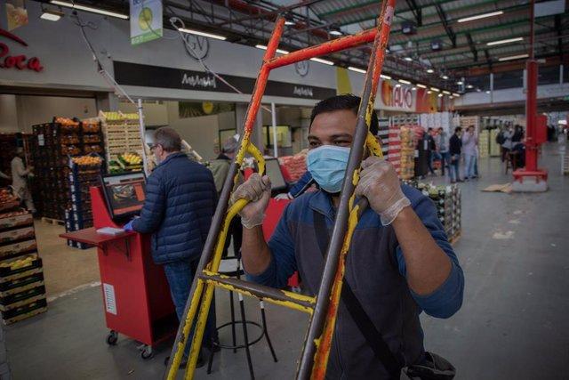 Un trabajador de Mercabarna transporta productos en cajas dentro del recinto. En Barcelona, Cataluña, (España), a 17 de abril de 2020.