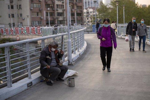 Imagen de varias personas en Shanghái con mascarilla por el coronavirus.
