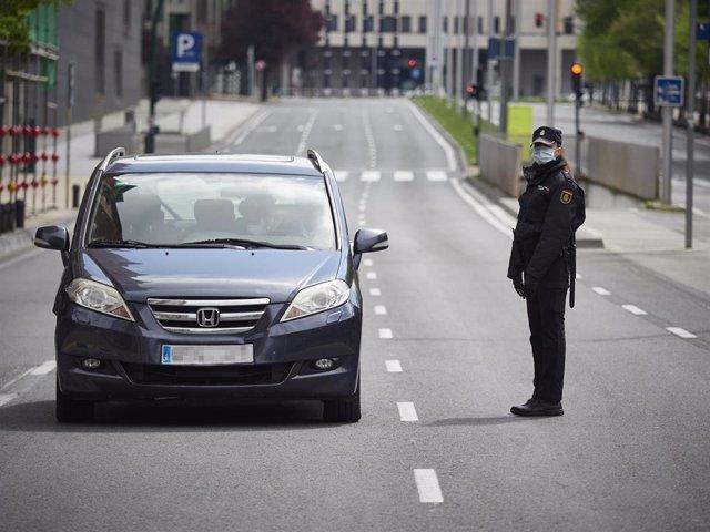 Una agente de la Policía Nacional protegida con una mascarilla en un control en la Avenida del Ejército de Pamplona durante el día en el que se reactiva la actividad laboral no esencial en las empresas cuyos empleados no puedan teletrabajar cuando se cu