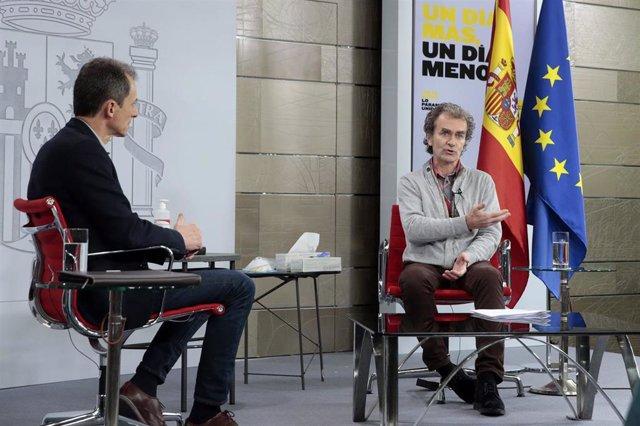(I-D) El ministro de Ciencia e Innovación, Pedro Duque, escucha la intervención del director del Centro de Coordinación de Alertas y Emergencias Sanitarias, Fernando Simón, en el encuentro #LaInfanciaPregunta, en Madrid (España) a 18 de abril de 2020.