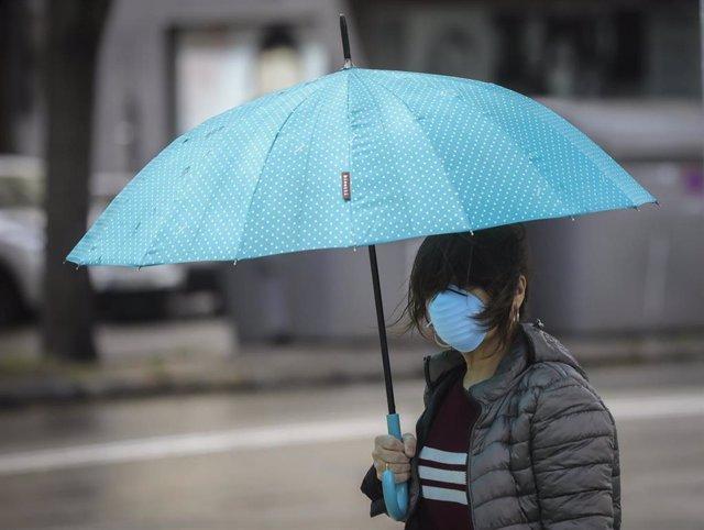 Una mujer protegida con mascarilla y guantes se resguarda de la lluvia bajo su paragüas en la quinta semana del estado de alarma por el coronavirus, Covid-19. En Sevilla (Andalucía, España), a 15 de abril 2020.