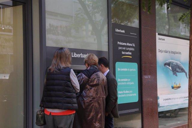 Tres personas efectúan una operación en un cajero de una oficina de Liberbank, que ha convocado a los sindicatos para negociar un nuevo Expediente de Regulación de Empleo (ERE), en Madrid, a 21 de octubre de 2019.