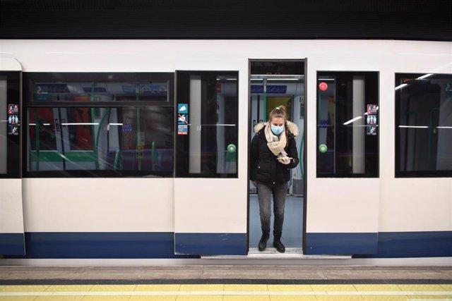 Una mujer protegida con mascarilla se baja de uno de los metros de la capital en un andén con círculos rojos en el suelo que Metro de Madrid ha colocado en sus estaciones para establecer distancia de seguridad entre viajeros ante la pandemia del Covid-1