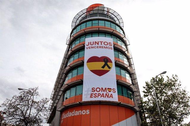 Ciudadanos despliega una lona con un crespón negro junto a la bandera de España en su sede nacional.
