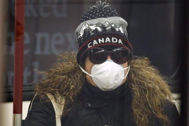 Mujer con mascarilla por el coonavirus en Toronto, Canadá