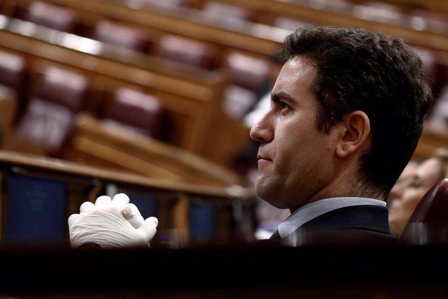 El secretario general del PP, Teodoro García Egea, escucha al presidente del Gobierno, Pedro Sánchez, durante su comparecencia ante un hemiciclo casi vacío para explicar la declaración del estado de alarma y las medidas para paliar las consecuencias de