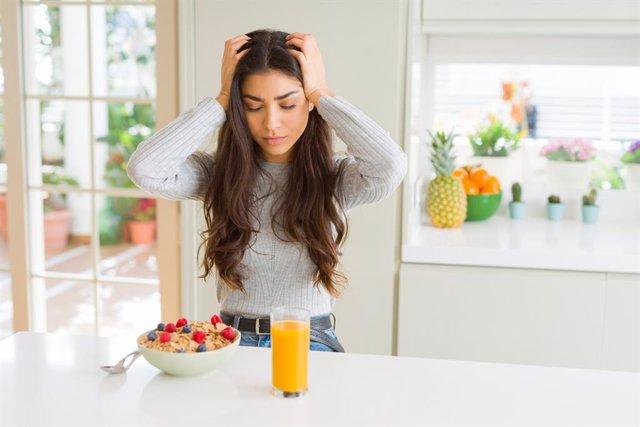 Joven desayunando con dolor de cabeza, migraña, cefalea.