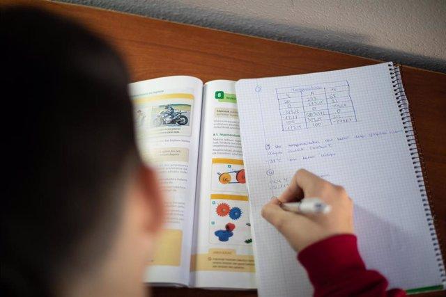 Un niño realiza sus deberes en su habitación durante el confinamiento por el Estado de Alarma