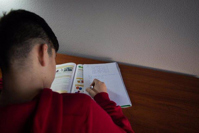 Un niño realiza sus deberes en su habitación durante el confinamiento por el estado de alarma, cuando España es el único país que no deja a los menores salir a la calle y un día después de que la ministra de Educación anunciara que el curso escolar acabar