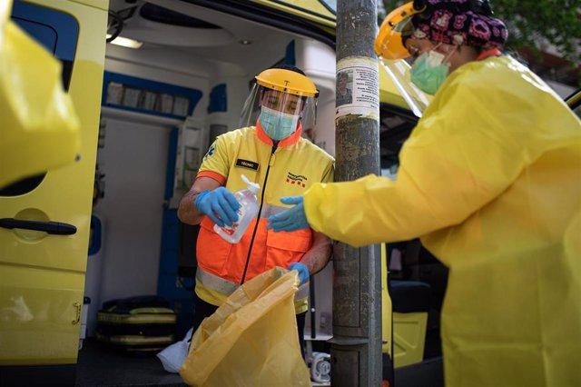 Dos técnicos del Sistema de Emergencias Médicas (SEM) de la Generalitat de Cataluña durante un servicio y limpieza de EPIs, en Barcelona/Catalunya (España) a 19 de abril de 2020.