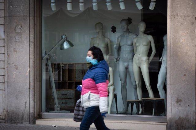 Una dona protegida amb una mascarilla passa al costat d'un aparador d'una botiga tancada a Barcelona durant l'estat d'alarma pel coronavirus.