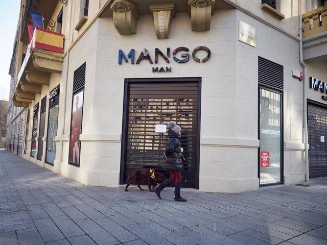 Una dona passeja al seu gos davant de la botiga PISPO tancada durant el terme de la segona setmana de confinament de l'estat d'alarma per coronavirus, covid-19. A Pamplona, Navarra (Espanya) a 29 de març de 2020.
