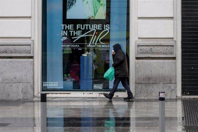 Una persona camina por una calle de Madrid donde las temperaturas han bajado estrepitosamente durante el segundo día de la entrada en vigor de la limitación total de movimientos salvo de los trabajadores de actividades esenciales, medida adoptada ayer por