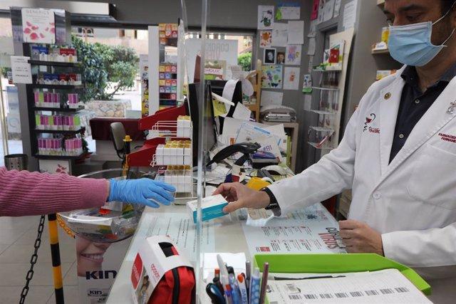 Un farmacéutico vende una caja de Paracetamol en su farmacia durante el segundo mes de confinamiento, en Madrid (España) a 20 de abril de 2020.